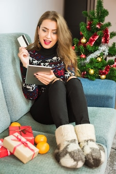 Молодая удивленная женщина, делающая покупки онлайн с таблеткой и кредитной картой на рождество