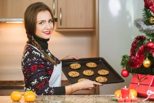 クリスマスツリーの近くに焼きたてのチョコレートクッキーを保持している若い幸せな女