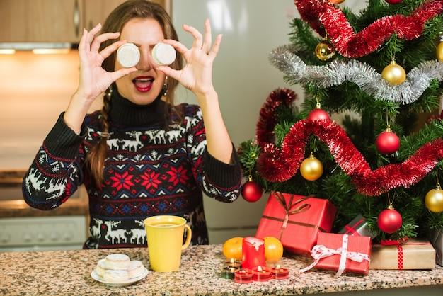 クリスマスツリーの近くにケーキを持つ若い幸せな女