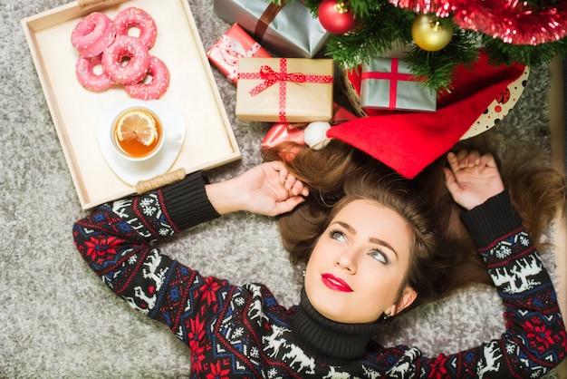 家の床に横たわっている鹿とセーターの若いかわいい幸せな女の子。