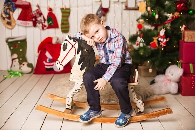 Маленький мальчик верхом на деревянной лошадке-качалке перед елкой