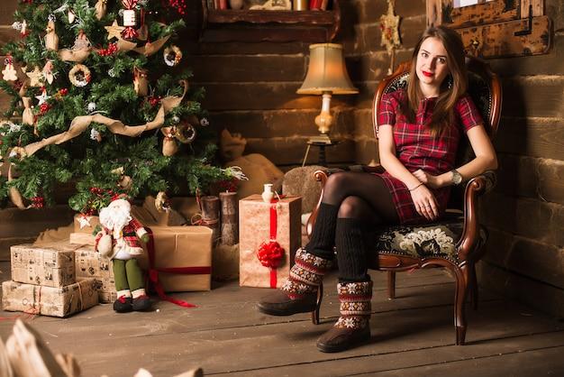Молодая девушка сидит рядом с елкой и подарками