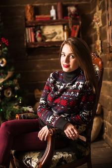 クリスマスツリーとギフトの隣に座っている若い女の子