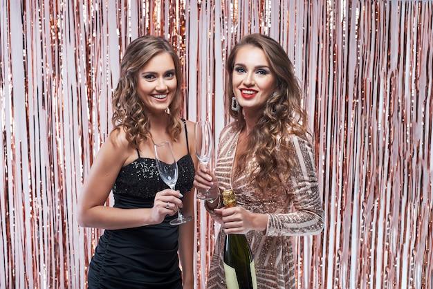 Две красивые элегантные женщины пьют шампанское на фоне сверкающих украшений