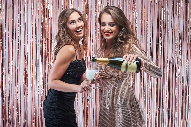 Молодая женщина наливает шампанское в бокалы.