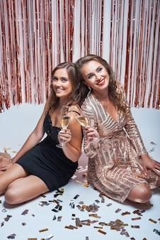 Молодые элегантные девушки весело и пили шампанское во время новогодней вечеринки.