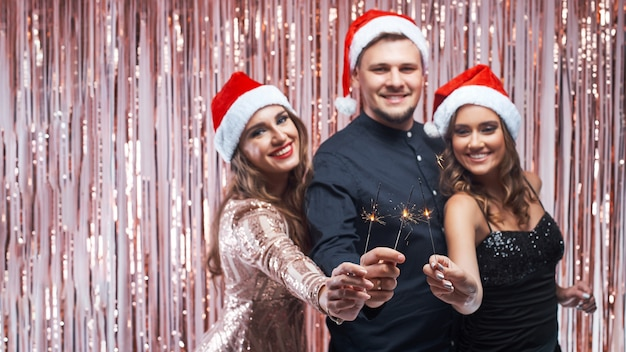 若い男と女性の手で花火でクリスマスを楽しんでいます。
