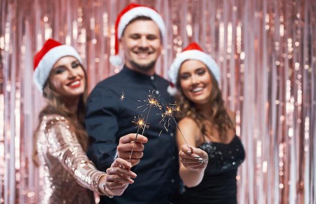 手で輝く新年のお祝いを楽しんでいる若い友人のグループ。