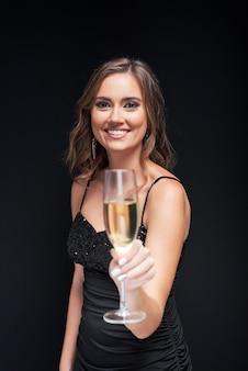 パーティーでシャンパンのグラスを持つ若いエレガントな女性。