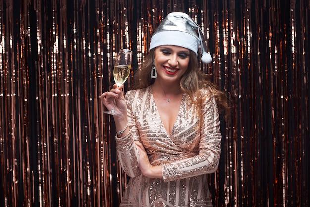 手にシャンパングラスと銀のサンタ帽子の若い幸せな女性の肖像画。