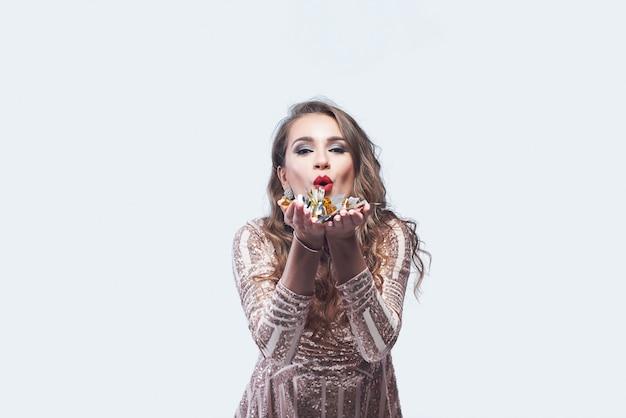 Молодая женщина в элегантном платье дует конфетти