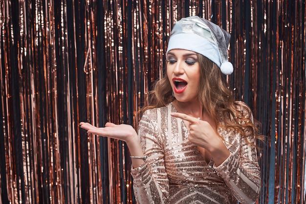 彼女の手で指で指しているサンタ帽子で若い興奮した女性の肖像画。