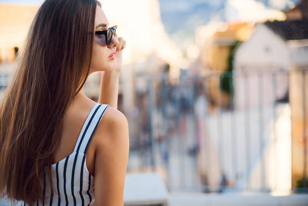 Фасонируйте портрет молодой женщины сидя и смотря в расстояние на улице.