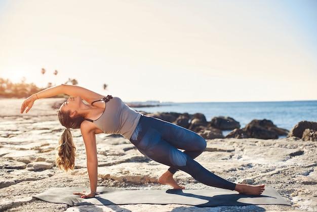 Йога молодой привлекательной женщины практикуя на пляже на заходе солнца.