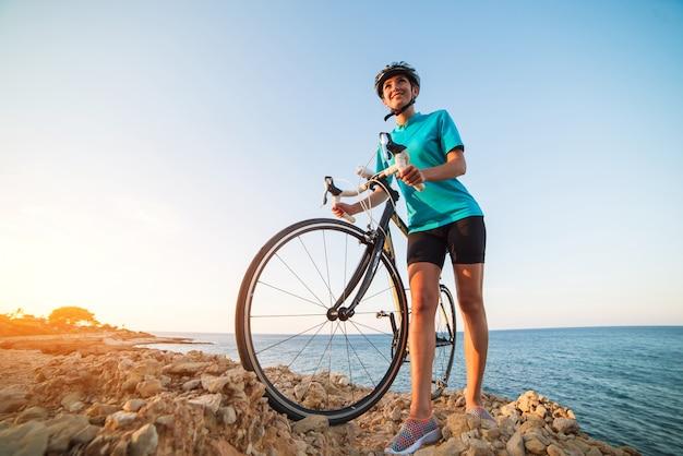 女性サイクリスト、岩の上に立っていると海を見て