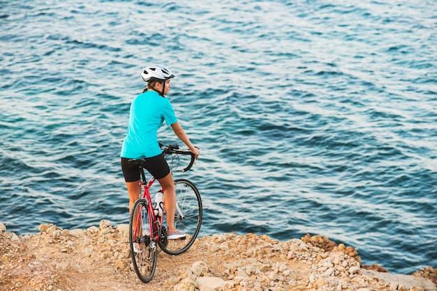 女性サイクリスト、丘の上に立っていると海を見て