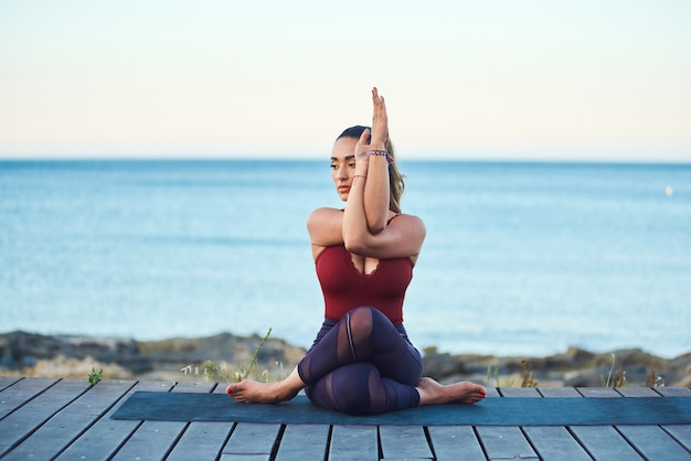 Красивая молодая женщина делая тренировки йоги на взморье против голубого моря.