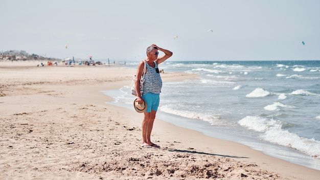 Красивый мужчина на летние каникулы, оставаясь на пляже и глядя на море.