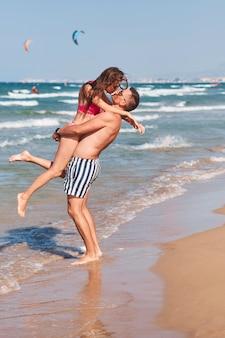 Молодая пара в любви, имеющие романтические нежные моменты на пляже.