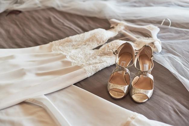白のエレガントなウェディングドレスと靴はベッドに横になっています。