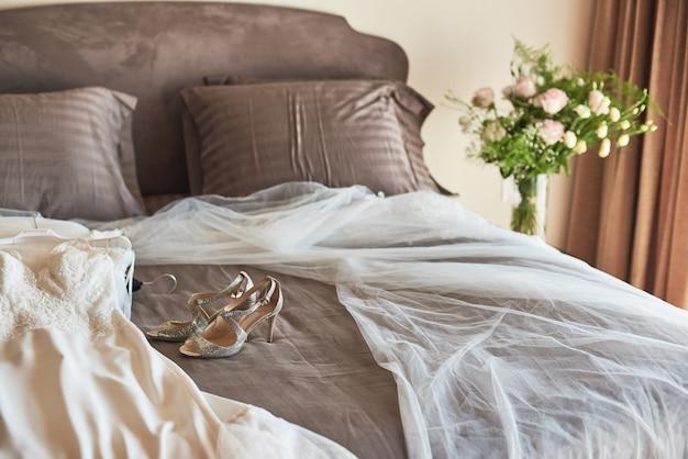 白のエレガントなウェディングドレス、ベール、靴はベッドに横になっています。