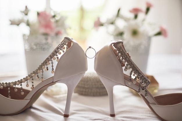 スタイリッシュな白い結婚式のブライダルシューズ、香水、花と宝石類。