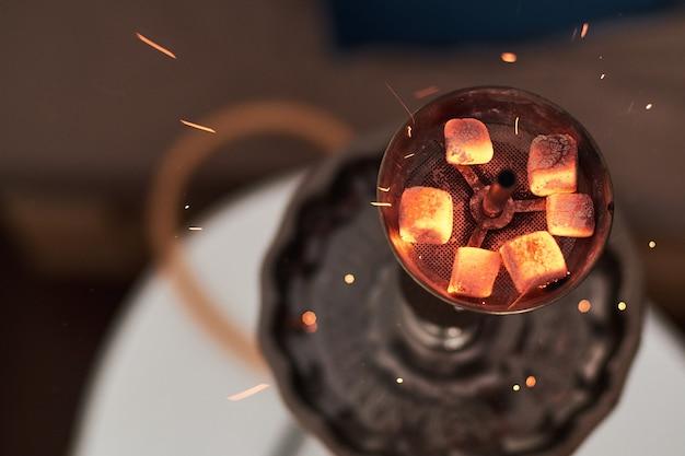 赤い熱い石炭とシーシャ水ギセルのクローズアップ。息を吐き出す。ココナッツ炭とシーシャの煙が入ったモダンな水ギセル。