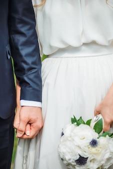 クローズアップ新婚夫婦はお互いの手を握っています。