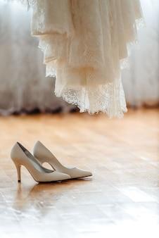 美しい結婚式の靴と木の茶色の床のドレス