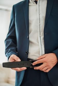 新郎の結婚式のスーツ、ベルトに手を繋いでいます。