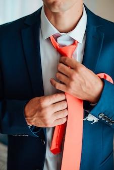 新郎は結婚式のスーツ、ネクタイに手を繋いでいます。