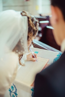 Рука невесты с ручкой, подписывающей свадебную лицензию