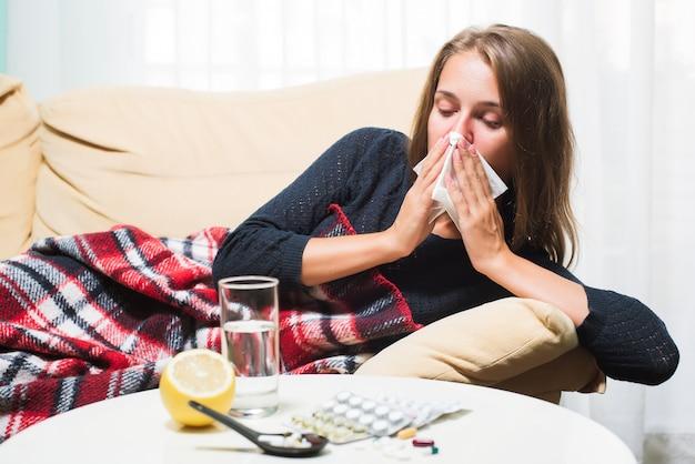 Больная женщина лежит на диване под шерстяным одеялом, чихая и вытирая нос