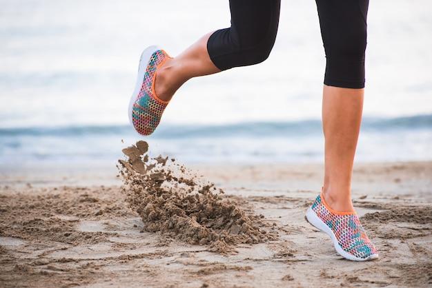 朝の砂の運動と日の出でビーチを走る女性の足のクローズアップ