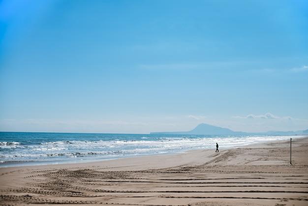 海に向かって歩く男のシルエット