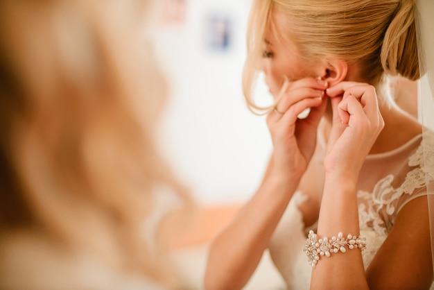 美しいエレガントな花嫁は彼女の水曜日の日の朝にイヤリングを着ています。