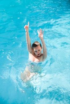 若いかわいい女の子はスイミングプールで楽しんでいます