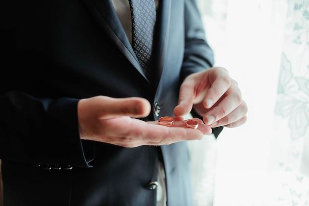 彼の手に金の結婚指輪と幸せな新郎。結婚式の日
