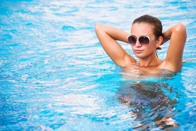Красивая загорелая сексуальная девушка в бикини позирует в бассейне