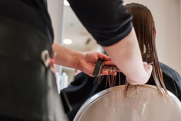 作業機の散髪のクローズアップをしているスタイリスト美容師