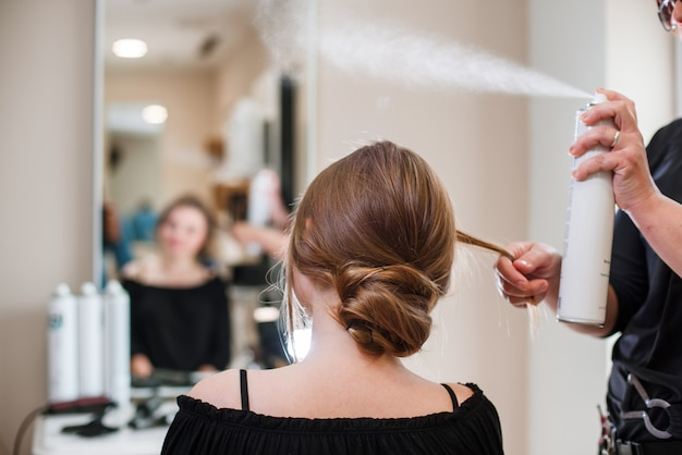 美容師のヘアスプレーで女性の髪を修正