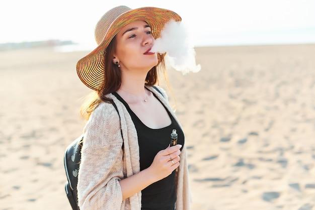ビーチで麦わら帽子の美しい若い女性