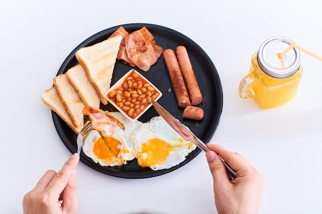 Человек ест традиционный полный английский завтрак