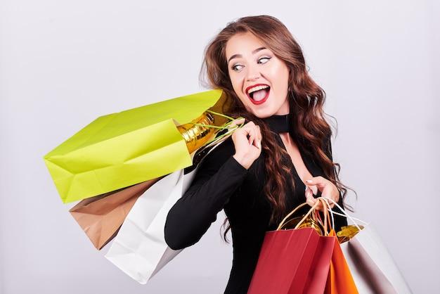 Стильная молодая брюнетка женщина, держащая красочные сумки