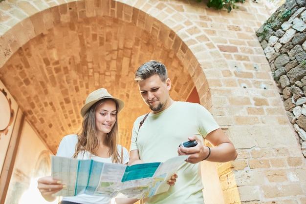 手で地図を持って旅行者の幸せな若いカップル