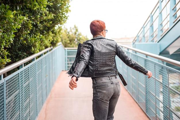 スタイリッシュな身に着けている少年、橋の上を回って