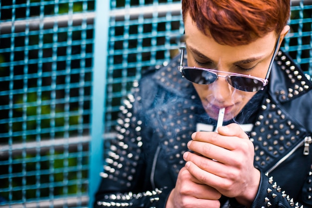サングラスをかけているスタイリッシュな若者の肖像はタバコを吸っています。