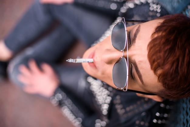 サングラスをかけているスタイリッシュな若者のトップビューはタバコを吸っています。