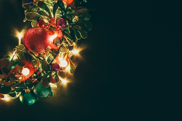 暗い木製の背景に装飾的な光とクリスマスの花輪
