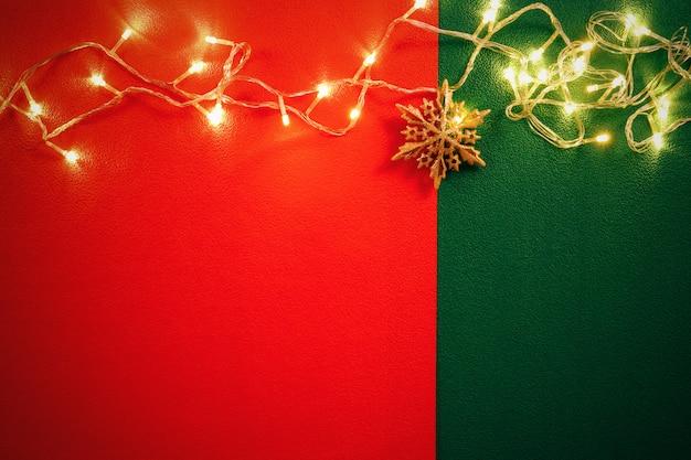 赤と緑の背景にクリスマスライトとパインスター